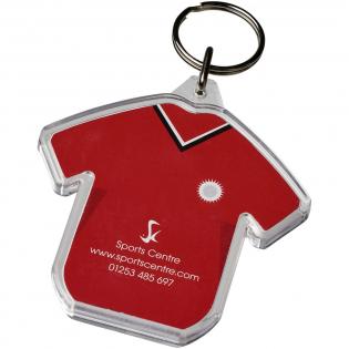 Porte-clés transparent en forme de t-shirt avec anneau fendu en métal. L'anneau en forme de boucle métallique présente un profil plat idéal pour les envois. Dimensions de l'insert pour impression: 6,0 cm x 3,8 cm.