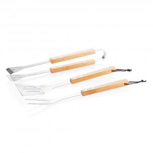 Set d'outils en acier inoxydable avec poignées en bambou. L'ensemble comprend une spatule, une fourchette à viande et une pince.