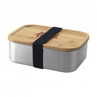 Lunchbox aus Edelstahl mit Bambusdeckel. Die Brotdose wird mit einem abnehmbaren elastischen Verschluss aus Polyester geliefert. Ein nachhaltiges und umweltfreundliches Produkt. Wird einzeln in einem Kraftkarton geliefert.